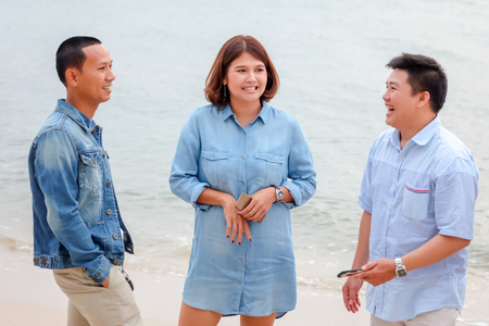 Asian men and women in blue tone are standing by the sea. Banco de Imagens