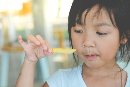 Cute Asian Girl Happy eating french fries. Reklamní fotografie - 113245874