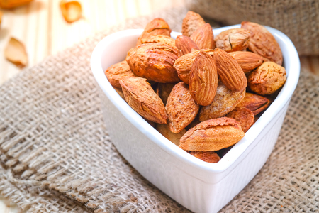 Almond nuts in the shell In a heart shaped bowl on sackcloth and wooden floor. Standard-Bild - 115375875