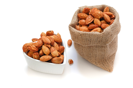 Almond nuts In a heart shaped bowl and sackcloth on on a white Standard-Bild - 115375879