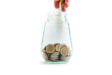 Place the coin into glass bottle on a white background. Save money for dream homes and holidays