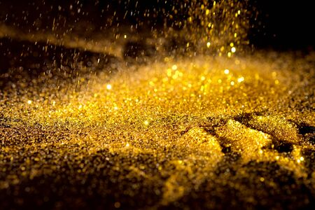 Sprinkle glitter gold dust sand in the dark textured abstract background elegant for Merry christmas and Happy new year