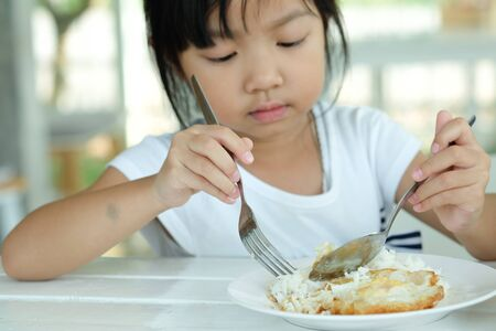 Cute Asian child eating rice with fried Egg Фото со стока