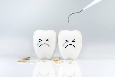 Teeth crying emotion with dental plaque tool ,Concept Dental care cleaning bacterial plaque