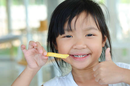 Asian child girl show thumb up and happy eating french fries Foto de archivo