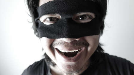 Robber man with black mask laughing, Thief robbery concept
