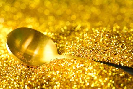 Golden spoon on glitter gold dust background ,Luxury and elegant concept Standard-Bild