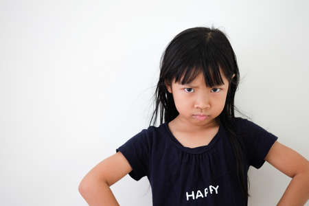 Asian girl shows anger on the face with arms hands on hips on a white background