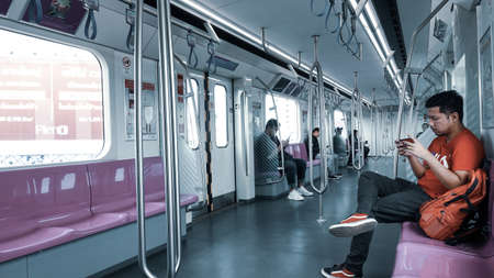 Bangkok Thailand - August 25, 2019: People put their hands on their mobile phones. Social addiction Not interested in people around while traveling in Electric train in Bangkok Thailand