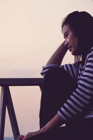 Asian woman is lonely and depressed sitting on the balcony. Banque d'images - 151495177