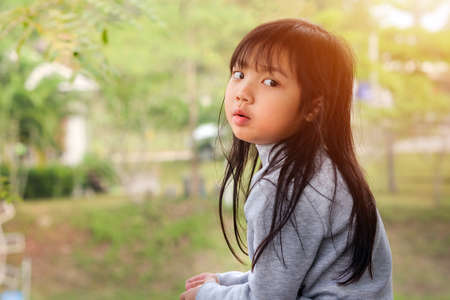 Asian child girl looking back on the side on green outdoor background