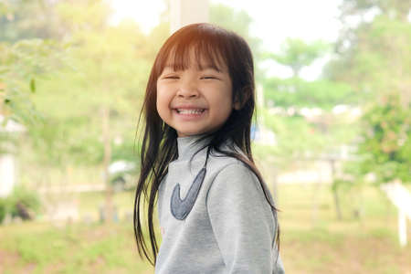 Asian child girl is smiling bright and cute on tree background outdoor