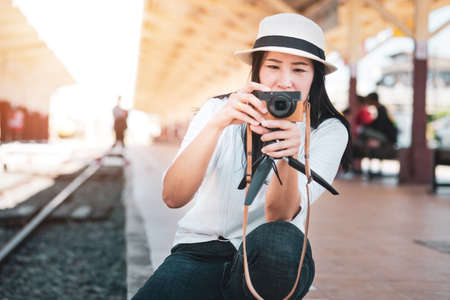 Asian woman tourist wearing a white T-shirt, wearing a hat, holding a camera and taking pictures at the train station