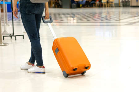 Asian woman's feet are walking to drag orange luggage in airport