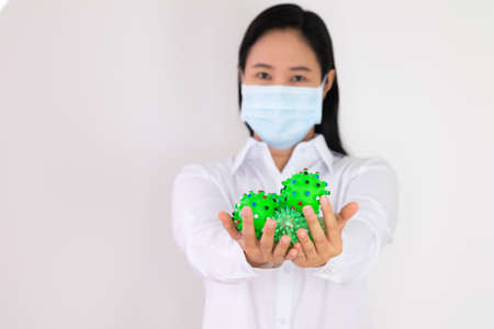 The hand of an Asian woman in a white doctor's outfit, holding a green ball with a virus-like , the idea of dealing with the virus Covid 19. Stock fotó