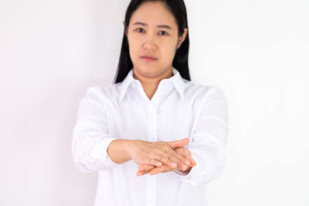 An Asian woman wearing a white shirt is washing her hands with alcohol gel to protect against corona virus or covid 19 on a white background.