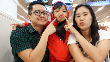 Asian lovely families parents and children about puckering lips are sitting and pointed at the cheek at the dining table. Stock Photo