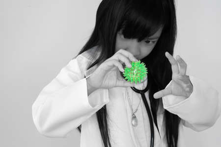Asian child girl in a white doctor's outfit is raising his hand to protect against a green, spiky green toy, the idea of a dangerous virus prevention Covid 19.