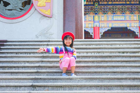 Asian child girl wearing jumpsuit jeans and T-shirts of many colors, smiling mood and sitting happily with love in temples, the concept of family lifestyle Stock fotó