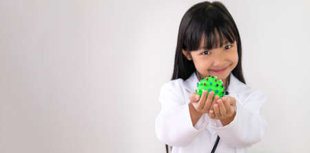 The hand of an Asian girl in a white doctor's outfit, holding a green ball with a virus-like and a smiling face, the idea of dealing with the virus Covid 19