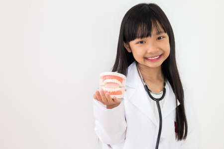 Asian child girl dressed in a doctor's outfit in her hand holding a dental model with a smiling face on a white background. Stock fotó