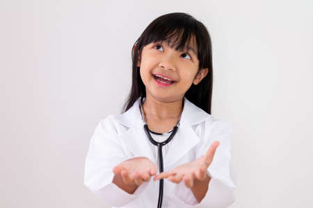 Asian child girl dressed in a doctor's uniform is carrying both hands with a smiling face on a white background. Stock fotó