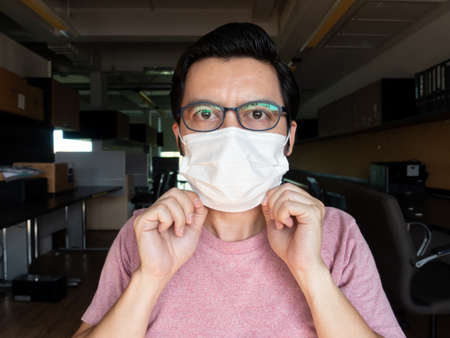 Asian men wearing pink T-shirts and wearing glasses are showing the right masks to prevent germs and viruses. , The concept of epidemic control of covid19