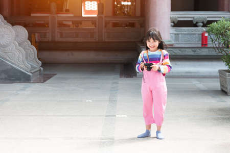 Asian child girl with a colorful T-shirt smiles and is using the camera happily.