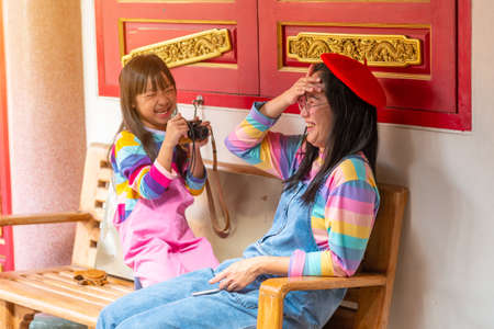 Asian mother and daughter are wearing jeans, T-shirts of many colors, smiling mood and standing happily photography with love in temples, the concept of family lifestyle.