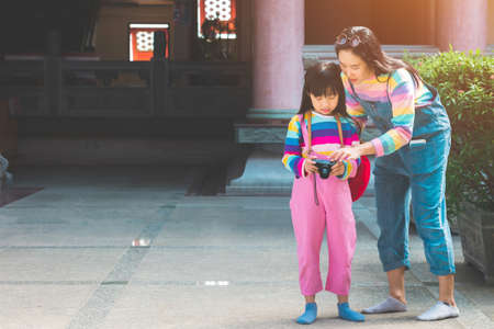 Asian child girl and mother with jumpsuit jeans and T-shirts colorful is taking pictures Stock fotó