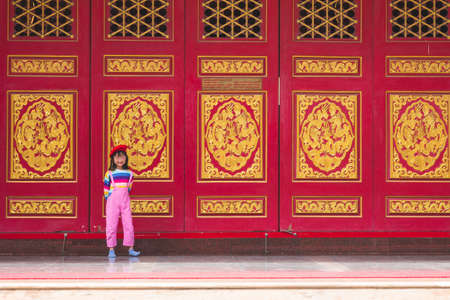 Asian child girl in pink  jumpsuit are standing and smiley face happy jam with love On the background of red door in the temple