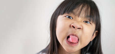 Asian child girl showing tongue out on a gray background. Standard-Bild