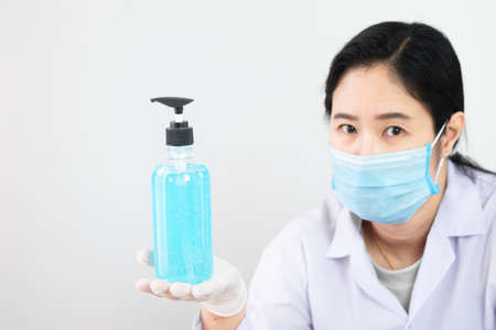 The bottle of alcohol sanitizer cleaner on hand of a nurse or doctor or physician assistant with selective focus