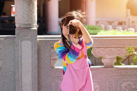 Asian child girl with jumpsuit pink jeans and T-shirts colorful is taking pictures