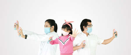 Asian families on a white background are strengthening to overcome the corona virus by wearing a mask and holding a bottle of alcohol for washing hands, cleaning or spraying items with the virus. Covid-19 stuck, superhero concept