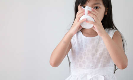 Asian girl in a white dress is drinking water or milk from a glass. Archivio Fotografico