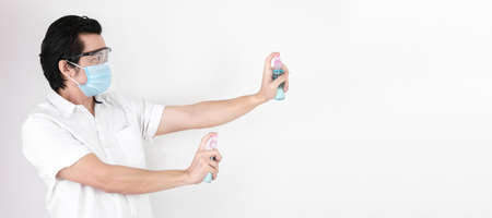 Asian man on a white background are strengthening to overcome the virus by wearing a mask and carrying alcohol bottles for washing hands, cleaning or spraying infected items. Covid-19 concept Stock Photo