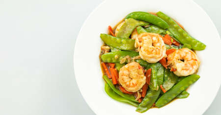 Stir-fried peas, put shrimp in a white plate on a white background.