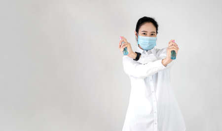 Asian woman are strengthening to overcome the virus by wearing a mask and carrying alcohol bottles for washing hands, cleaning or spraying infected items. Covid-19 Banco de Imagens