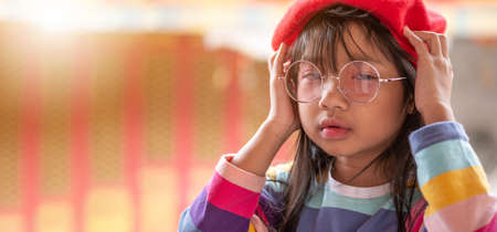 Asian child girl dressed up in a rainbow colored T-shirt. Wear red lens glasses and wearing a red hat with a smiley face and good mood Banco de Imagens