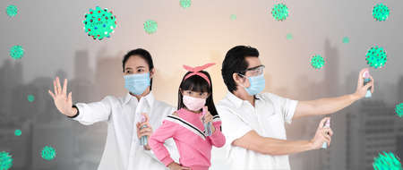 Asian family on city background are strengthening to overcome the virus Covid-19 by wearing a mask and carrying alcohol bottles for washing hands, cleaning or spraying infected items.