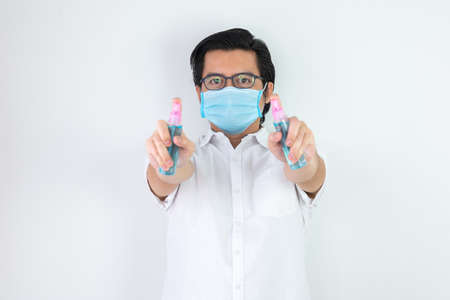Asian man on a white background are strengthening to overcome the virus by wearing a mask and carrying alcohol bottles for washing hands, cleaning or spraying infected items. Covid-19 concept