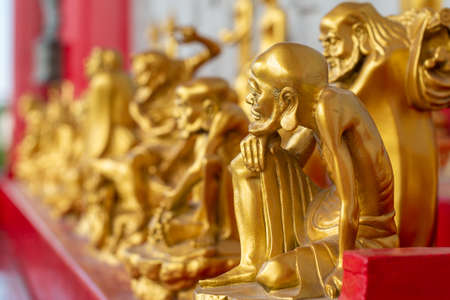 The statue of the golden Buddhist saint in the temple for people to pay respect