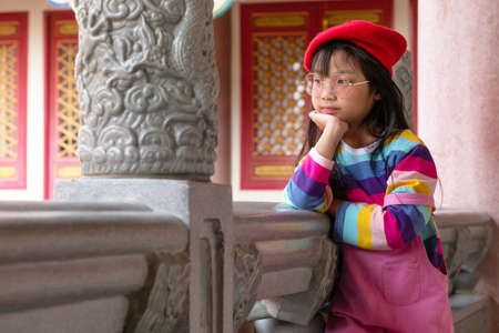 Asian child girl resting her chin on hand and dressed up in a rainbow colored T-shirt wear red lens glasses and wearing a red hat with a smiley face and good mood