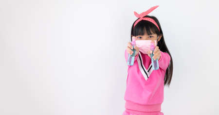 Asian child girl are strengthening to overcome the virus by wearing a mask and carrying alcohol bottles for washing hands, cleaning or spraying infected items. Covid-19
