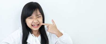 Asian child girl in a white shirt is smiling and pointing at the teeth with braces on a white background
