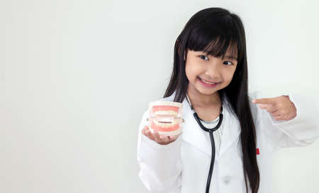 Asian child girl wearing a medical uniform and is holding a dental model in hand with a smiling face on a white background 免版税图像