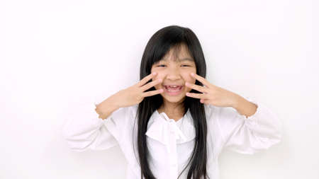 Asian child girl is smiling cute and uses her finger to act like a cat on a white background.