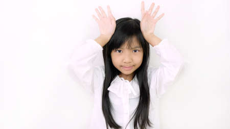 Asian child girl is smiling cute and uses her finger to act like a deer on a white background.