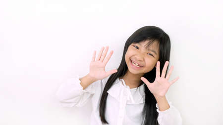Asian child girls are smiling cute and showing ten fingers on a white background. Stock Photo